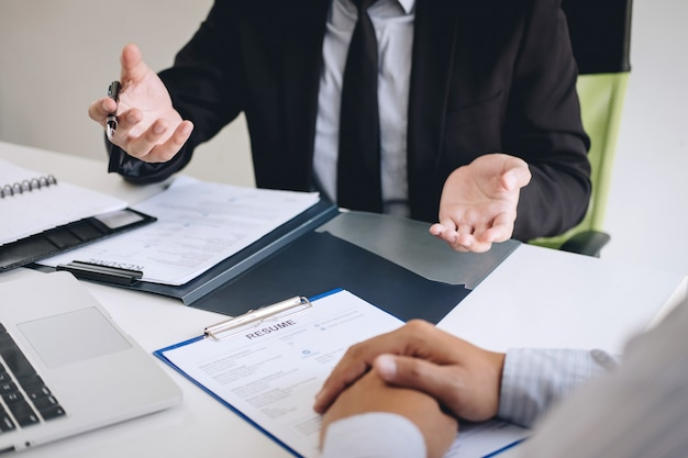 Работодатель или вербовщик держит чтение резюме во время разговора о своем профиле кандидата, работодатель в костюме проводит собеседование, менеджер по трудоустройству и концепции найма