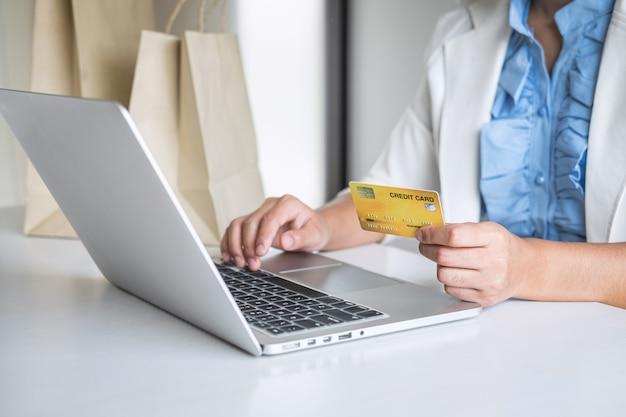 Деловая женщина-потребитель держит кредитную карту и печатает на ноутбуке для совершения покупок в интернете и оплаты, совершает покупки в интернете, оплачивает онлайн, устанавливает сети и покупает технологию продуктов