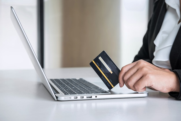 ビジネスの女性消費者はクレジットカードを保持し、オンラインショッピングや支払いのためにラップトップに入力する