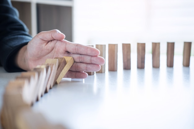 ビジネスにおけるリスクと戦略、落下を止める手のイメージ倒れた連続ブロックからの木製ブロックドミノ効果、安定性への予防と開発