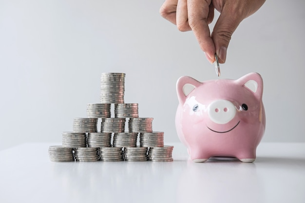 コインの山の積み重ねと、貯金箱での成長と貯蓄を計画するためのピンクの貯金箱にコインを置く手の画像、将来の計画と退職基金のためのお金の節約