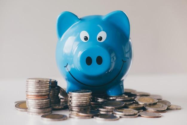 Изображения укладки монет ворс и синей улыбающейся копилки для выращивания и сбережений с копилкой