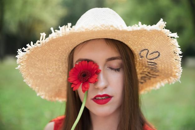 若い魅力的な女の子は、夏の野の花の花束を保持しています。