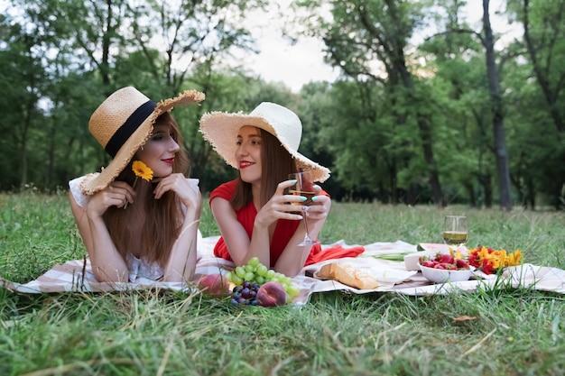 都市公園でのピクニックに若い魅力的な女の子。
