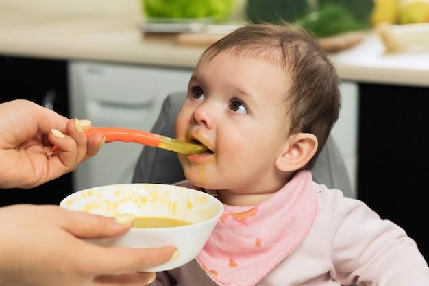 給餌。子供の椅子にスプーンで食べる愛らしい赤ちゃん。