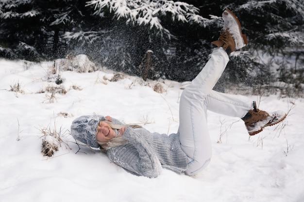 長い白い髪の若い美しい女性は雪玉を果たしています。