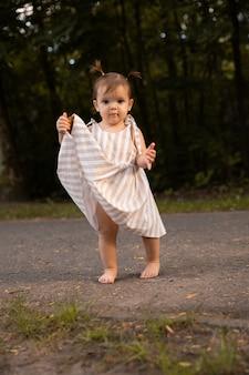緑豊かな芝生の上で裸足で走るアビーガールは、公園で楽しんでいます。
