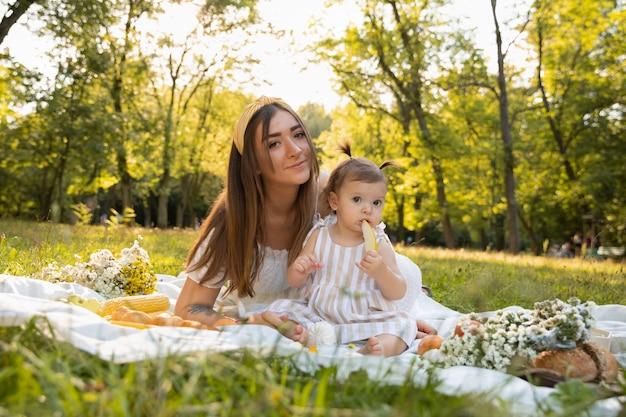 若いお母さんと彼女の小さな娘が都市公園でピクニックをしています。