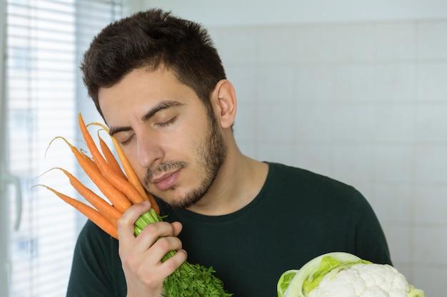 男は愛情を込めて新鮮な野菜を抱きしめます。