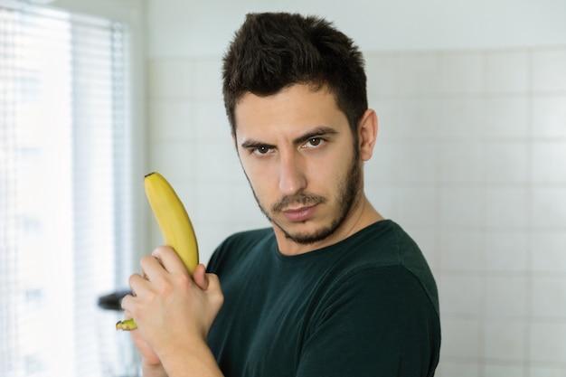 バナナが武器であることを想像して彼のキッチンで楽しんで若いハンサムな男。