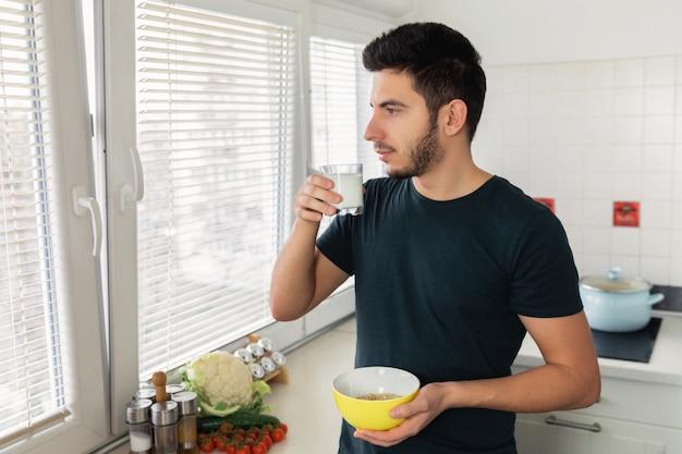 若いハンサムな男は、自宅の台所で朝食を取っています。