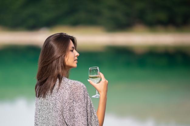 白いドレスの美しい少女は、グラスからワインを飲みます。彼女は湖のほとりにあり、ピクニックや野外レクリエーションを楽しんでいます。