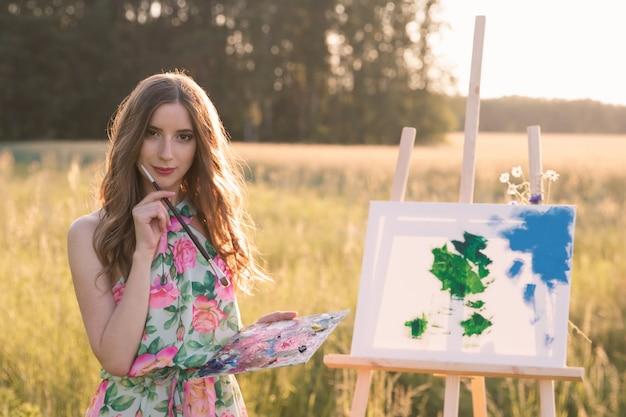 長い自然な髪の若い美しい女性が屋外で絵を描く