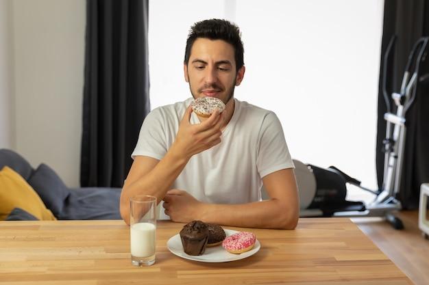 Молодой красивый парень сидит за столом и ест пончики.