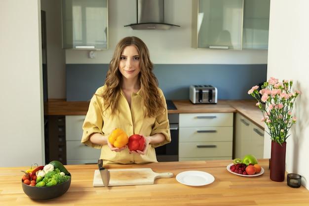 手にピーマンを保持している美しい少女。女性は新鮮で健康的な野菜のサラダを準備します。