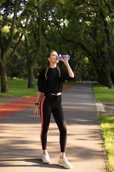 Красивая молодая кавказская женщина в носке фитнеса разрабатывая в парке.