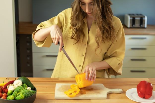 長い髪の美しい少女は、ピーマンをスライスします。女性は新鮮で健康的な野菜のサラダを準備します。