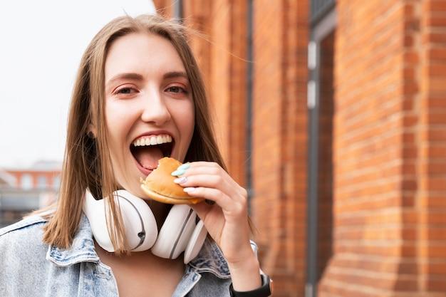 若い女の子が路上でハンバーガーを食べています。彼女はおいしいおやつを楽しんでいます。