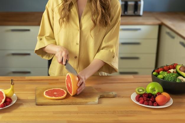 美しい少女はグレープフルーツを切っています。女性が美味しくて健康的なフルーツサラダを準備します。