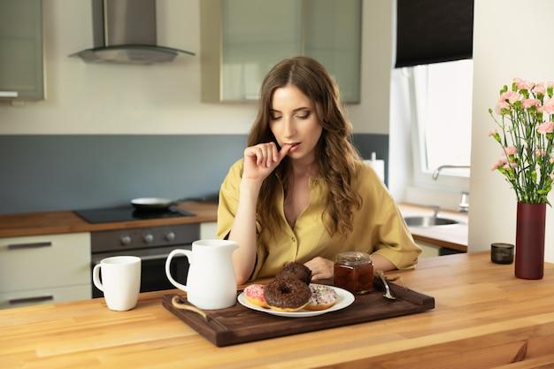 自宅の台所で朝食を持っている美しい少女。女の子は不健康で高カロリーの食べ物を食べます。