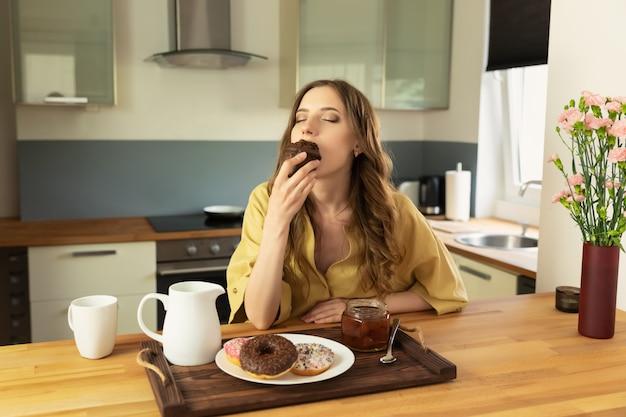 美しい少女は、キッチンで自宅で朝食を食べています。彼女は朝のコーヒーを飲み、チョコレートマフィンを食べます。