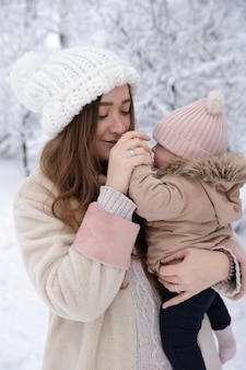 小さな子供を持つ若い母親が雪の中で遊んでいます。彼らは楽しんで、降雪を楽しんでいます。冬は外を歩きます。