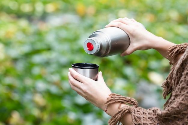 魔法瓶からマグカップで温かい飲み物を注いで、ハイキング中にお茶を飲む女性。