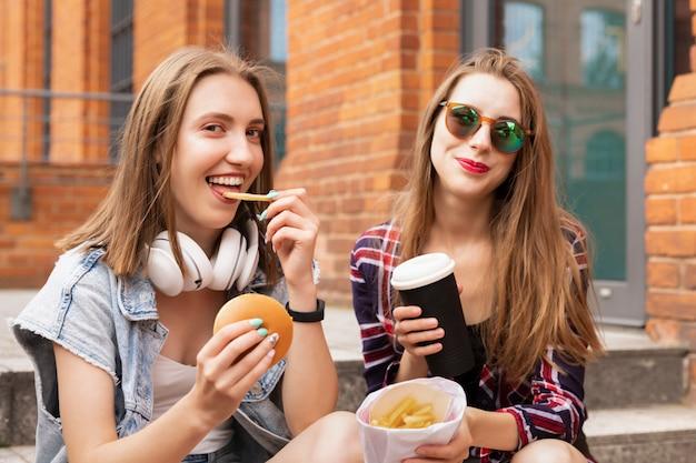 Две красивые молодые девушки едят фаст-фуд прямо на улице, они веселятся, разговаривают и кормят друг друга вкусными вещами.