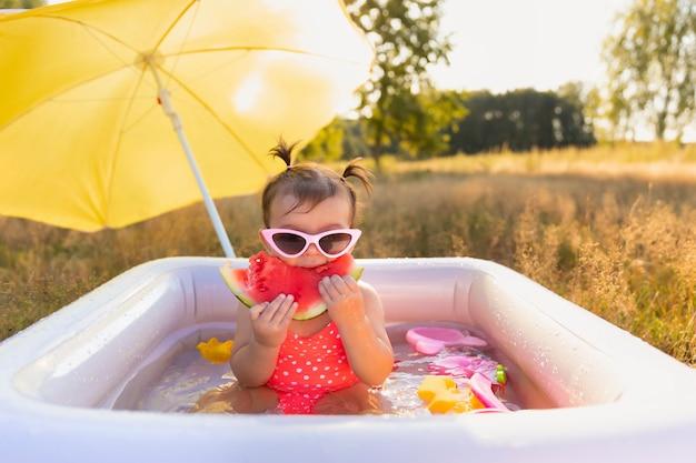 膨脹可能なプールで遊ぶ少女。