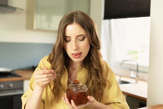 美しい少女は、キッチンで自宅で朝食を食べています。彼女は朝のコーヒーを飲みます。