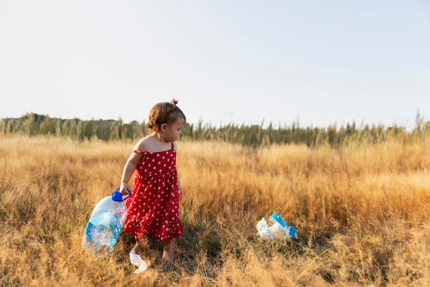 小さな女の子は森に散らばっているゴミを集めます。