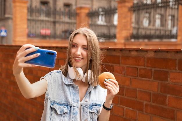 若い女の子が通りでハンバーガーを食べています。彼女はおいしいおやつを楽しんでいます。