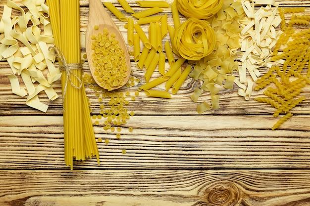 ヴィンテージの木製のテーブルにイタリアのパスタトップビューのコレクションを持つフレーム