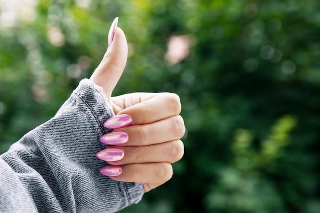 美しいピンクのマニキュアの女性の手はクラスを示しています。