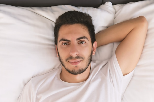 彼のベッドで寝ている若いハンサムな男。