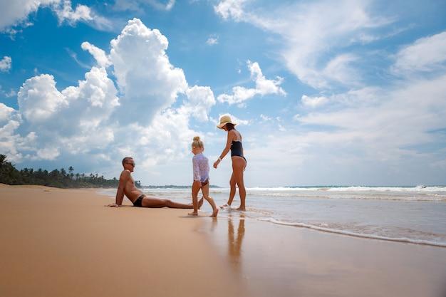 幸せでアクティブな家族、ママ、パパ、小さな娘がビーチで遊んでいます。