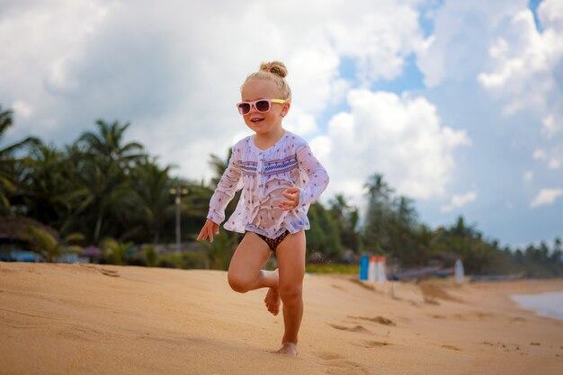 小さな女の子は、ビーチで砂の上を実行します。