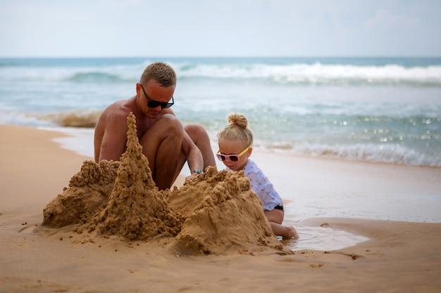 Молодой отец с ребенком строит замок из песка на берегу океана.