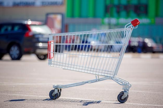 Пустая продуктовая корзина на стоянке у супермаркета.