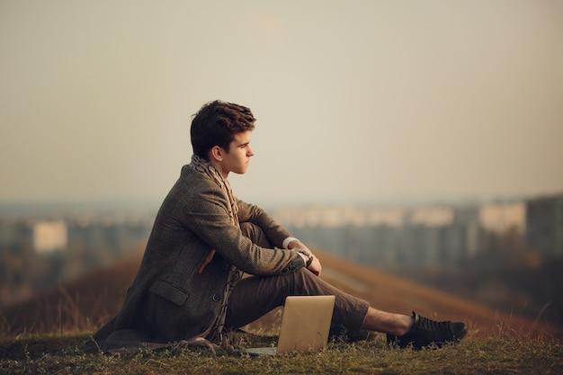 遠くの都市のシルエットに対して、草の上に座っているハンサムで成功した青年実業家の肖像画。おしゃれなコートを着た男のスタイリッシュなイメージ。