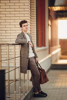 Молодой парень стоит с сумкой, крупным планом, против кирпичной стены.