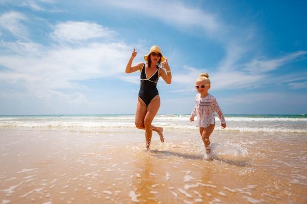 幸せで活動的な家族、ママと小さな娘が水の上を走り、ビーチで遊ぶ。