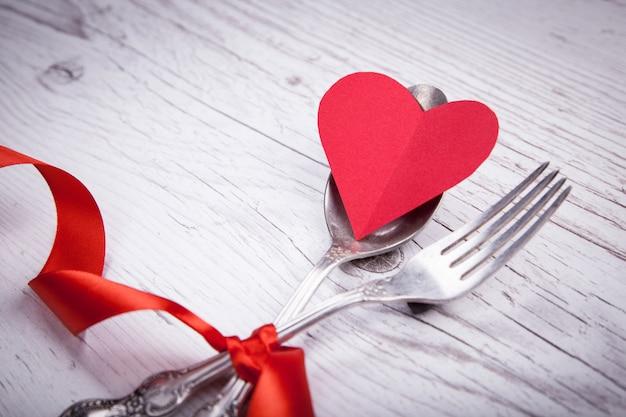 ビンテージスプーンと赤いテープと木製のテーブルの上のバレンタインデーのための心とフォーク。