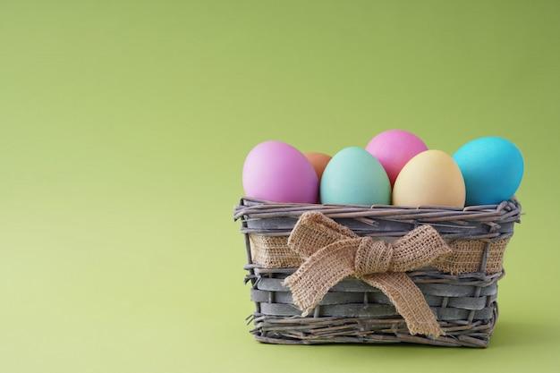 美しいカラフルな卵の木製バスケットハッピーイースター、グリーティングカードの良い空白。