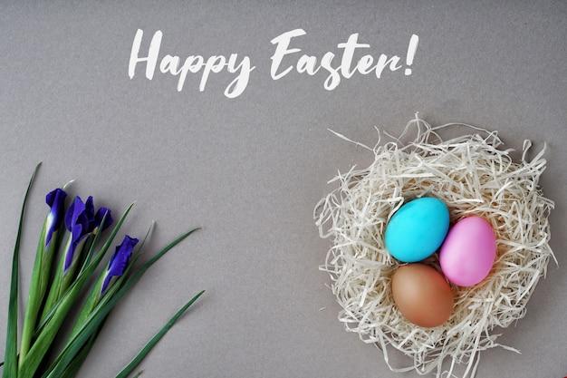 グリーティングカードハッピーイースター。着色された卵と巣、アイリスの花。良いコンセプト。