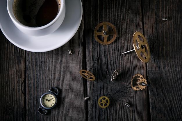 古い時計、時計仕掛け、歯車、ネジ、木製の板に未完成のコーヒーカップ。良いアイデアのヴィンテージ、内側からの時間。上からの眺め。