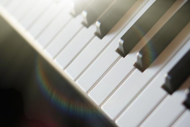 太陽光線マクロの電子シンセサイザーピアノキーボード。色付きの光線のハイテク。