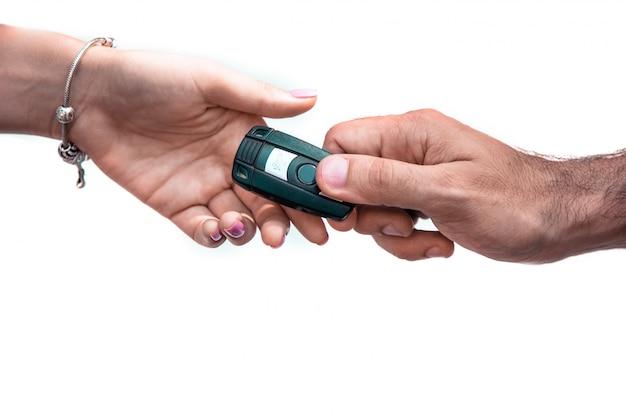 Хорошая идея, человеческая рука, передающая ключи от машины другой руке на белом изоляте