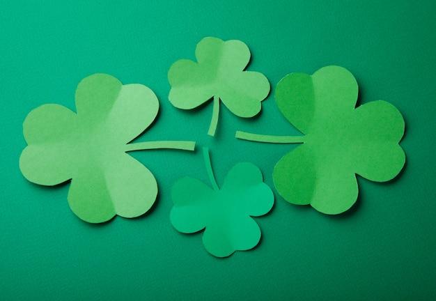 緑色の背景でクローバーの紙の葉。楽しいセント・パトリック・デイを過ごしてね。