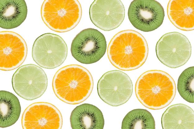 キウイ、ライム、オレンジのカラフルなパターン。柑橘系の果物とスライスしたキウイの平面図です。